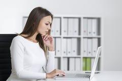 一名严肃的妇女的侧视图膝上型计算机的 库存图片