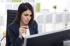一名严肃的妇女的画象在一个绿色和白色办公室 免版税库存图片
