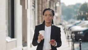 一名严肃的非裔美国人的女实业家的画象衣服的,走在城市,饮用的咖啡和使用附近 股票录像