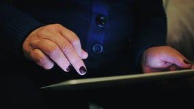 一名中年妇女使用她的片剂 免版税库存照片