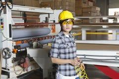 一名亚裔女性产业工人的画象有拿着的导线与机械在背景中 免版税库存照片
