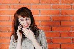 一名俏丽的妇女谈话由手机,微笑,在的砖墙 免版税图库摄影