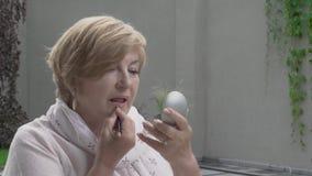 一名俏丽的年迈的妇女的移动式摄影车特写镜头大阳台的 她拿着一个小的镜子 股票视频
