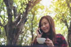 一名兴高采烈的美丽的亚裔妇女举行和谈话在巧妙的电话在室外,当喝咖啡有绿色自然背景时 免版税库存照片