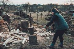 一名农村妇女在与轴的冬天射击收获的树木头 免版税库存照片