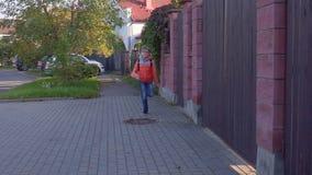 一名十岁的学生跑对,从有一个背包的学校在他的后面和微笑 慢的行动 影视素材
