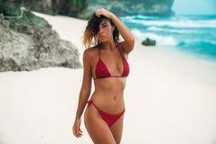 一名华美的妇女的画象红色比基尼泳装的在与白色沙子的海滩 有一个性感的被晒黑的身体的美丽的女孩在a 免版税库存照片