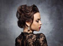 一名华美,可爱的妇女的画象有美丽的耳环的 免版税库存照片