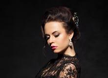 一名华美,可爱的妇女的画象有美丽的耳环的 免版税库存图片