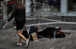 一名可怜的妇女请求在一条商业街的金钱在巴塞罗那 库存图片