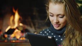一名可爱的妇女的画象:那与片剂一起使用 在背景中是被点燃的壁炉 概念:舒适和 股票录像