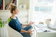 一名可爱的妇女的画象在桌,莲花姿势上 库存图片