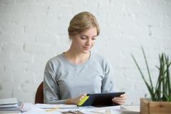 一名可爱的妇女的画象有一种片剂的在书桌 免版税库存图片