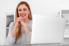 一名可爱的妇女看照相机,当坐在家时书桌在工作场所或 坐在服务台 库存照片