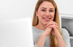 一名可爱的妇女看照相机,当坐在家时书桌在工作场所或 坐在服务台 库存图片