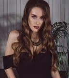 一名可爱的时髦,性感的棕色毛发的妇女的画象一件黑礼服的有开放肩膀的在演播室 工作室照片 Fashi 免版税库存照片