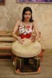 一名可爱的深色头发的妇女播放小手鼓 免版税库存照片