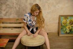 一名可爱的白肤金发的妇女播放小手鼓 免版税图库摄影