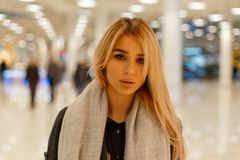 一名可爱的逗人喜爱的年轻白肤金发的妇女的画象有性感的嘴唇的有在一件外套的美丽的灰色眼睛的在户内葡萄酒围巾 库存照片