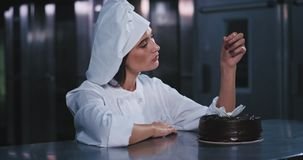 一名可爱,吸引人和穿着体面的年轻面包师妇女迷人拿着樱桃在非常恰好装饰 股票录像