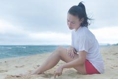 一名哀伤的妇女在与她深刻的想法的沙子看下来 库存照片