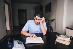 一名哀伤的学生勉强读一本书在他的屋子里 执行家庭作业 在家教 免版税库存照片
