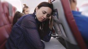 一名在飞行中在飞机上睡觉的女子靠在前座 股票视频