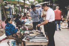 一名地方老挝小山部落妇女卖商品在每日早晨市场上在琅勃拉邦, 2017年11月13日的老挝, 免版税图库摄影
