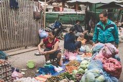 一名地方老挝小山部落妇女卖菜在每日早晨市场上在琅勃拉邦, 2017年11月13日的老挝, 免版税库存照片