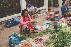 一名地方老挝小山部落妇女卖菜在每日早晨市场上在琅勃拉邦, 2017年11月13日的老挝, 免版税库存图片