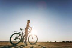 一名坚强的妇女的剪影在沙漠区域坐一辆自行车的一套五颜六色的衣服的 球概念健身pilates放松 背景蓝天 图库摄影
