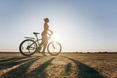 一名坚强的妇女的剪影在沙漠区域坐一辆自行车的一套五颜六色的衣服的 球概念健身pilates放松 背景蓝天 免版税库存图片