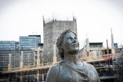 一名坚强的妇女的雕象有建造场所的在背景中在奥斯陆 免版税库存图片