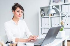 一名女实业家的特写镜头画象她的工作场所的与个人计算机一起使用,看在照相机,佩带的办公室衣服 免版税库存照片