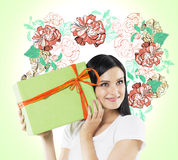 一名好奇妇女设法猜测什么是在绿色礼物盒里面 五颜六色的花剪影在光g被画 免版税库存照片