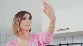 一名好妇女在厨房里拿着一个智能手机,做selfie 股票录像