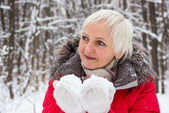 一名好资深妇女的画象冬天雪木头的在红色外套 免版税图库摄影