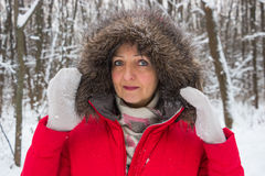 一名好资深妇女的画象冬天雪木头的在红色外套 免版税库存图片