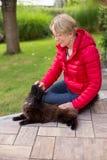 一名好年长妇女热情地抚摸她的猫 免版税库存照片