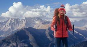 一名妇女以在山顶部的背包休息和享受谷的看法 库存照片