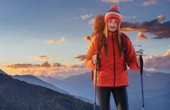 一名妇女以在山顶部的背包休息和享受谷的看法 免版税库存照片