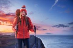 一名妇女以在山顶部的背包休息和享受谷的看法 免版税库存图片