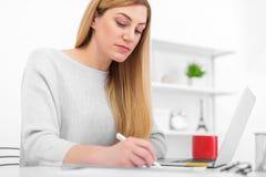 一名妇女在一个白色办公室坐在桌和写上 使用膝上型计算机的一位小姐填装在的文件 免版税图库摄影