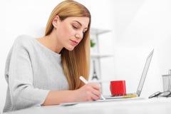 一名妇女在一个白色办公室坐在桌和写上 使用膝上型计算机的一位小姐填装在的文件 库存图片