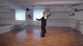 一名妇女在一个空的演播室采取舞蹈课 这是她的爱好 她在一种好心情排练 设法做360 影视素材