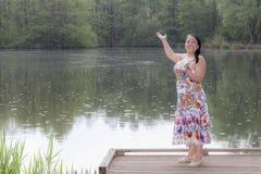 一名妇女在一件白色礼服和在湖的岸的多彩多姿的装饰的图象有黑色头发的 免版税库存图片