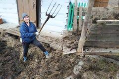 一名妇女在乡下从坑早期的春天选择肥料到城市 库存图片