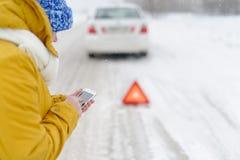 一名妇女在冬天叫对紧急情况服务 库存照片