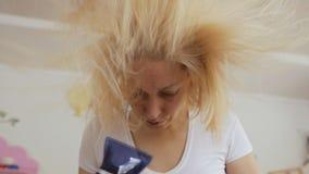 一名妇女在她的四十年代内烘干她的有吹风机的被染的金发 股票录像