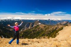 一名妇女在山天夏天 岩石路线 蓝天 雪和 库存图片
